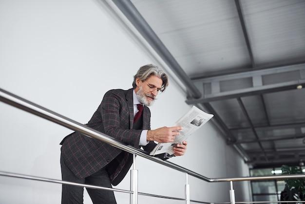 정장을 입고 회색 머리와 수염을 기른 고위 사업가는 문서를 손에 들고 있습니다.