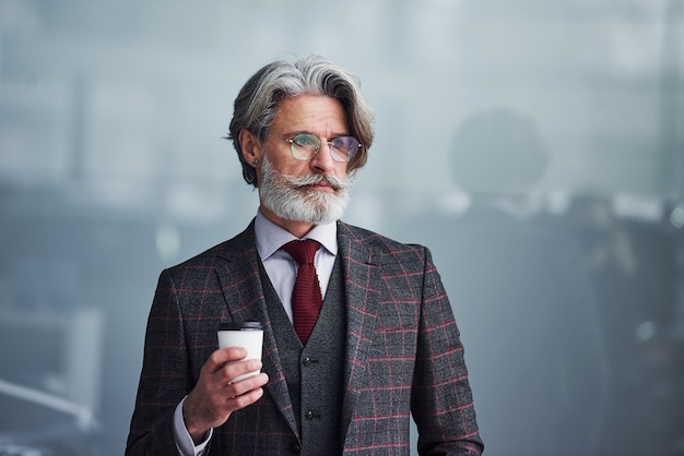 양복을 입고 회색 머리와 수염을 가진 넥타이를 한 고위 사업가가 컵을 들고 서 있습니다.