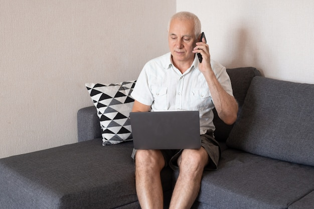 Senior businessman is talking on the mobile phone while working in home office