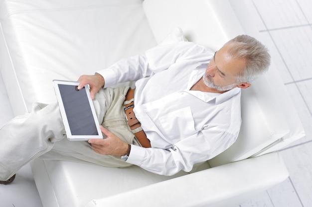 Senior businessman looking at digital tablet screen sitting on sofa.