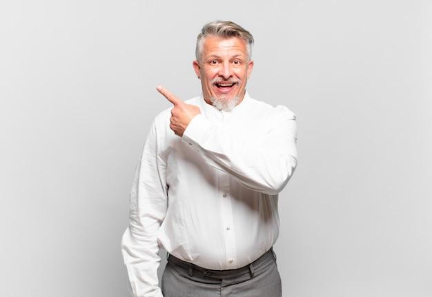 スペースをコピーするために横と上を指して興奮して驚いたように見えるシニアビジネスマン