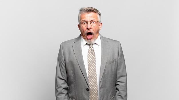 非常にショックを受けたり驚いたりして、すごいことを言って口を開けて見つめているシニアビジネスマン