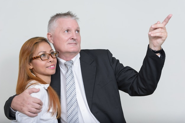 Senior businessman and mature asian businesswoman together against white