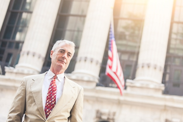 Senior businessman in new york with american flag