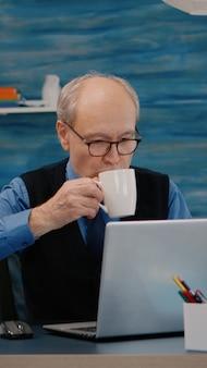 Старший бизнесмен, читая отчеты, сидя перед ноутбуком