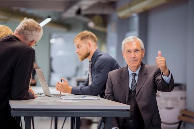 사무실에서 논의하는 그의 팀 앞에 앉아 엄지 손가락 기호를 보여주는 수석 사업가