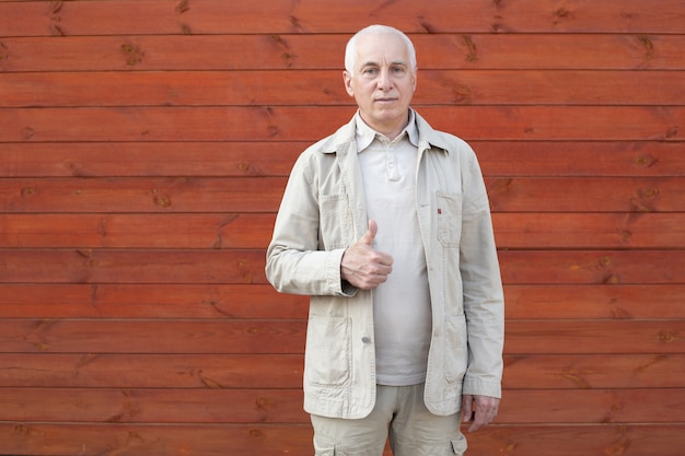 Senior businessman showing thumb up on wooden wall background