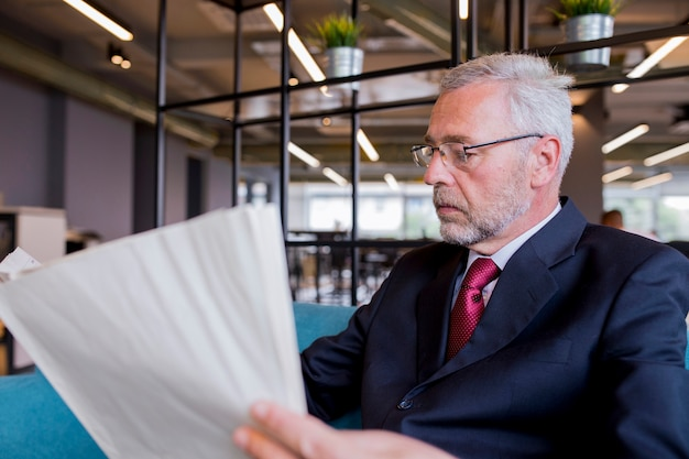 Senior businessman sitting reading newspaper in the office