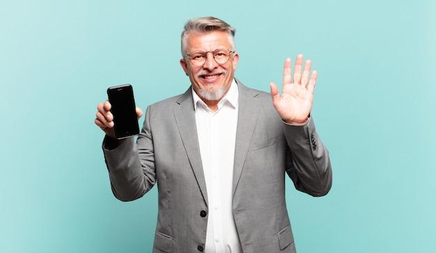 Старший бизнесмен счастливо и весело улыбается, машет рукой, приветствует и приветствует вас или прощается