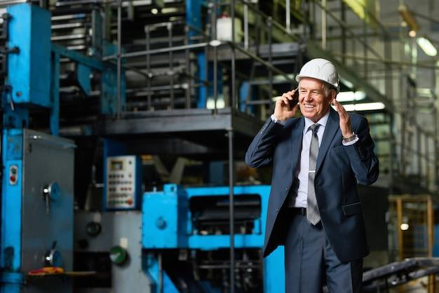 Senior businessman speaking by phone in factory
