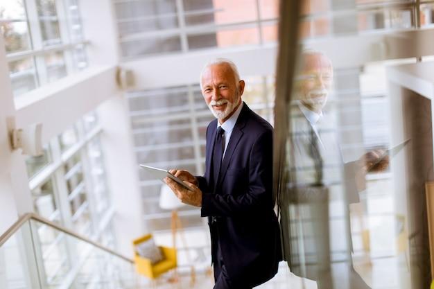 Senior businessman using digital tablet in the office