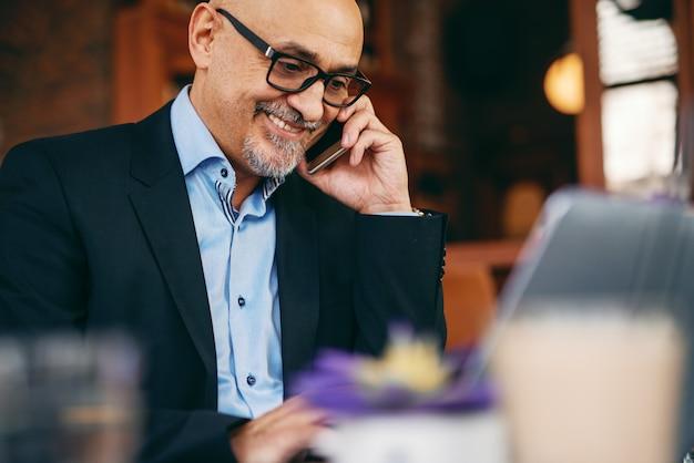 カフェに座っている間スマートフォンとラップトップを使用して上級ビジネスマン