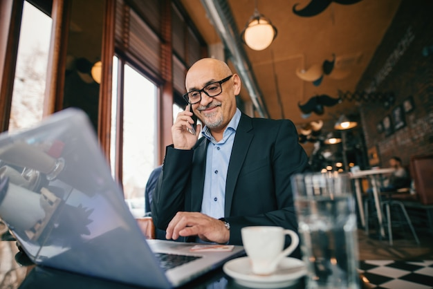 Senior businessman using smart phone and laptop while sitting in cafe