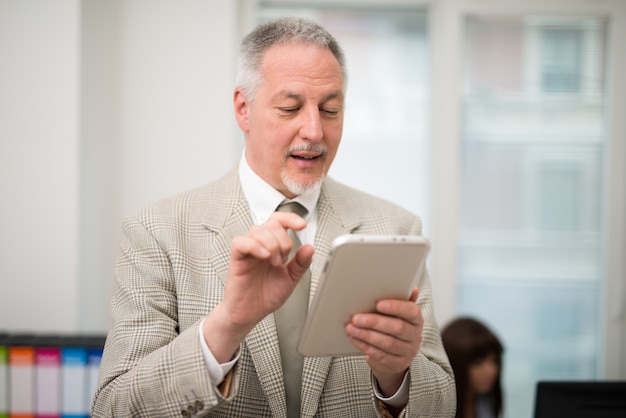 Senior businessman using a tablet in his office