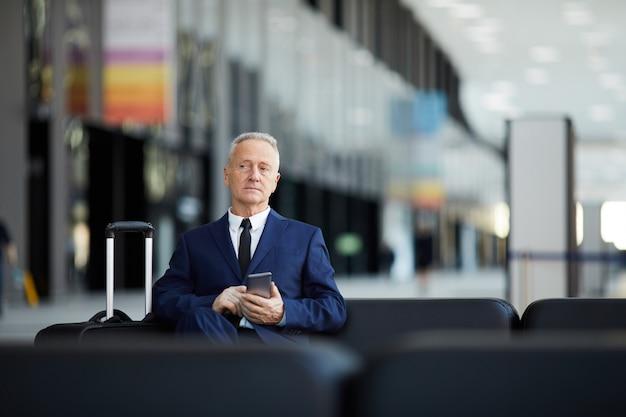 Старший бизнесмен ждет в аэропорту