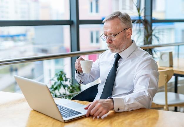 Старший бизнесмен носит белую рубашку и пьет кофе возле большого окна с видом на город