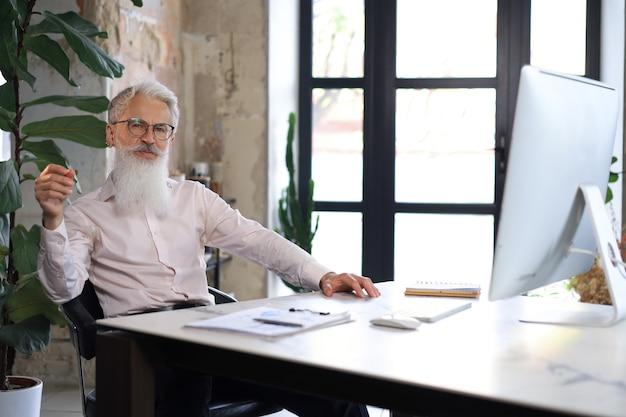 彼のオフィスの机でコンピューターに取り組んでいるスタイリッシュなひげを持つシニアビジネスマン。