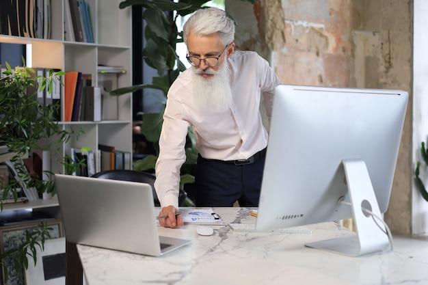 彼のオフィスの机でラップトップコンピューターで作業しているスタイリッシュなひげを持つシニアビジネスマン。