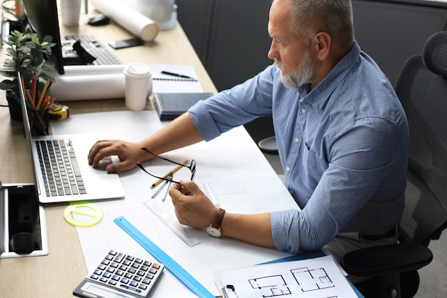 彼のオフィスの机でラップトップコンピューターで作業しているスタイリッシュな短いひげを持つシニアビジネスマン。