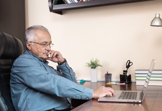 수석 사업가 집에서 작동합니다. 안경을 쓴 노인이 노트북을 사용하여 원격으로 일하고 있습니다. coronovirus 개념 중 원격 작업