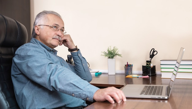 Senior businessman work at home. an elderly man in glasses is working remotely using a laptop. remote work during coronovirus concept