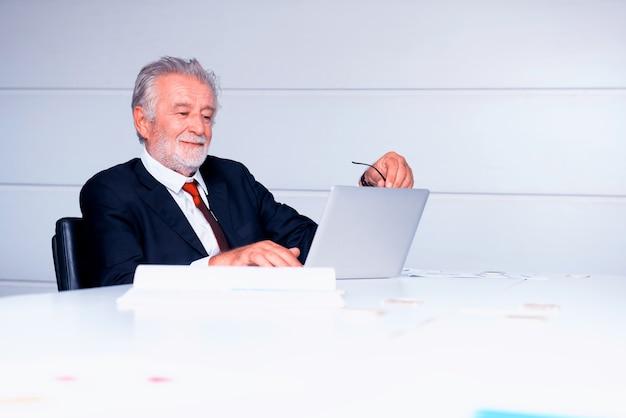 사무실에서 일하는 수석 사업가. 노트북에서 비즈니스 이익 차트를 찾고 있습니다.