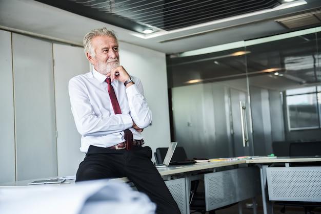 Старший бизнесмен, работающий в офисе. подумайте о пенсии и бонусах.
