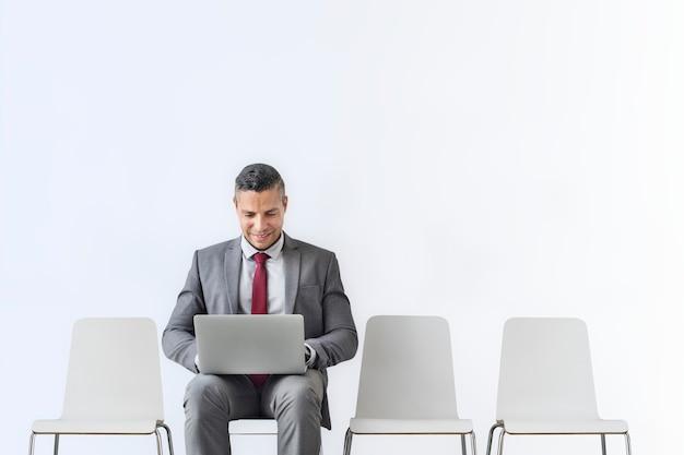Uomo d'affari maggiore che lavora su un computer portatile in camera
