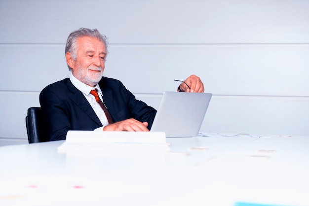 Senior businessman working in office. looking on business profits chart on laptop.
