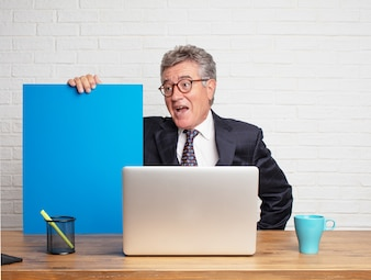 Senior businessman working  with his laptop and showing an empty