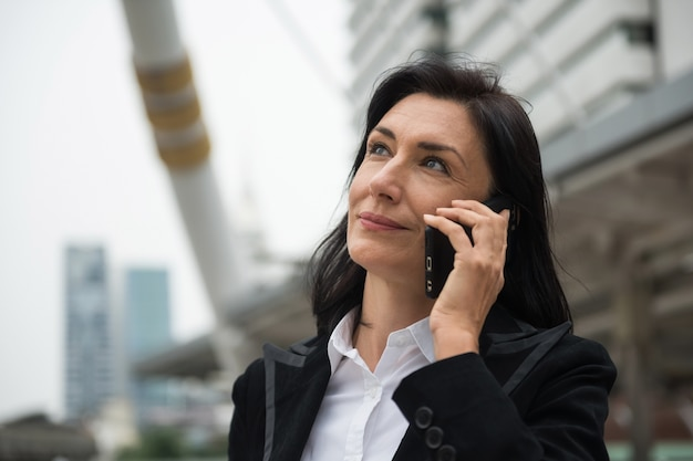 Senior businesswoman discuss project by smartphone
