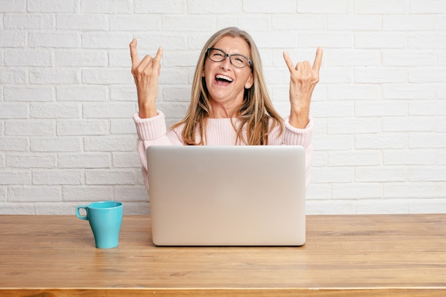 Senior businesswoman singing rock, dancing, shouting, gesturing in a rebellious, angry way.