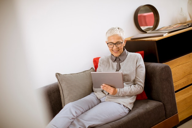 Senior businesswoman sitting with tablet on sofa