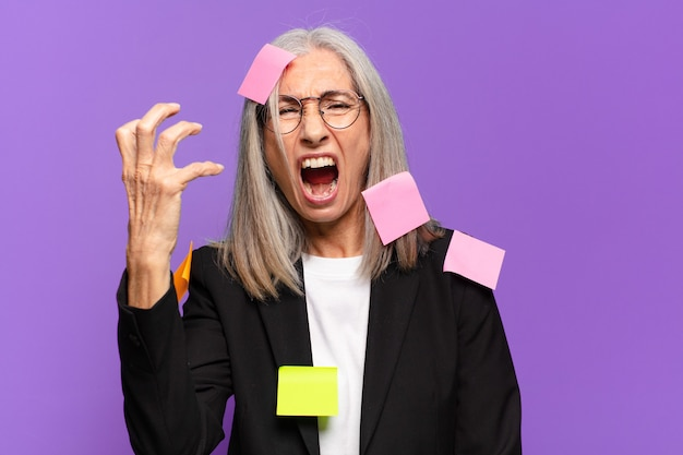 Senior businesswoman with adhesive post. humorous business concept