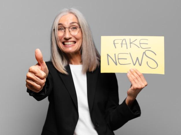 フェイク ニュース バナーを持つシニア ビジネスウーマン