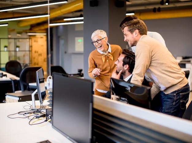 オフィスで若いビジネス人々と一緒に働く上級実業家