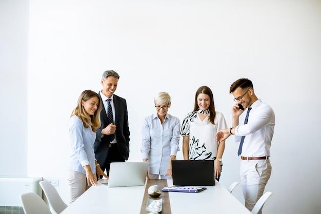 Старший бизнесмен, работая вместе с молодыми деловыми людьми в офисе