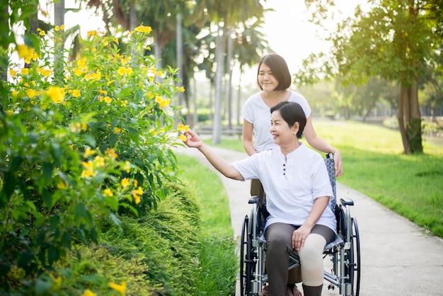 シニアケア保険の概念、介護者は屋外で車椅子に座っている高齢者のアジアの女性に注意してください