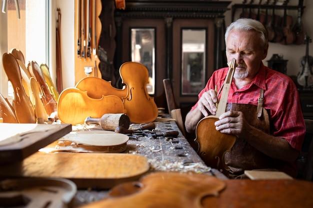 Старший плотник собирает детали скрипичного инструмента в своей столярной мастерской.