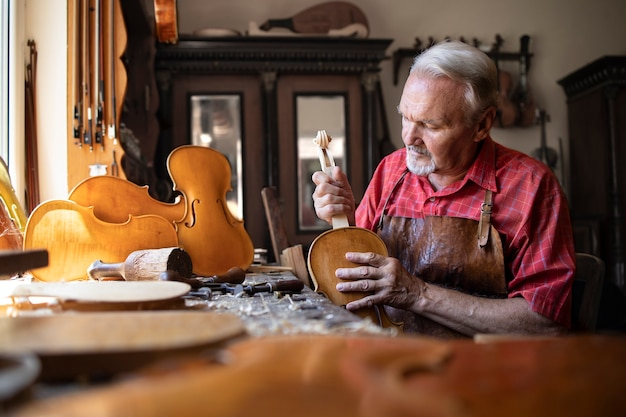 Senior carpenter assembling parts of violin instrument in his carpenter's workshop