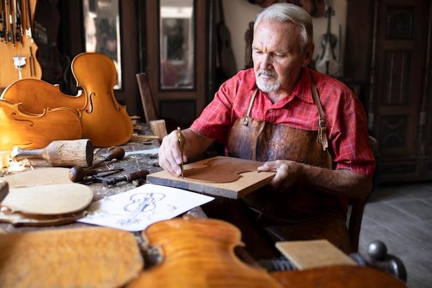 Старший плотник делает скрипку музыкальный инструмент в своей старинной столярной мастерской.