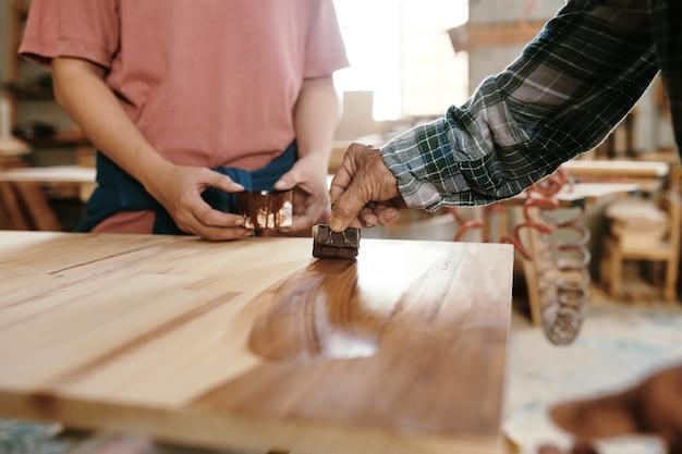 견습생에게 샌딩된 나무 판자에 기름을 바르는 방법을 보여주는 수석 목수