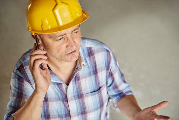携帯電話を使用するシニア大工