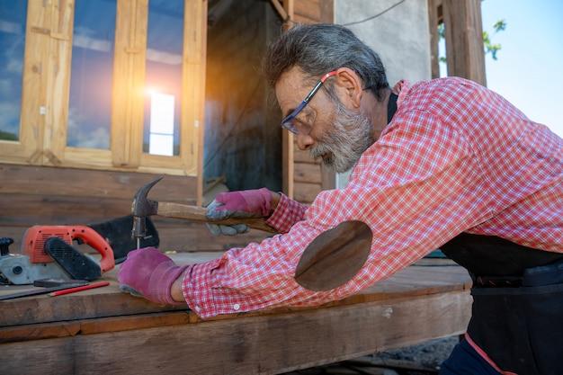 Старший плотник с помощью молотка ударил по гвоздю для сборки дерева.