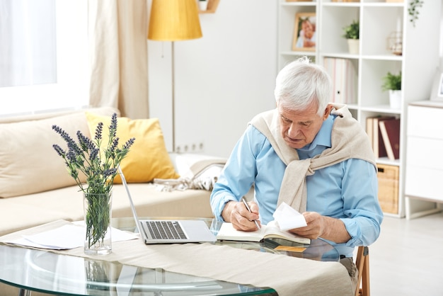 Senior casual man with white hair making notes in notebook while working at home by table in front of laptop