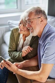 スマートフォンを使用して自宅で年配の白人カップル、彼らは一緒に座って休憩し、笑顔
