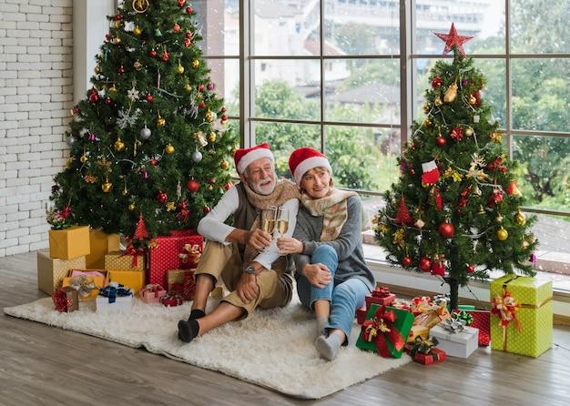 冬の居心地の良いリビングルームで飾られたクリスマスツリーの間に座ってシャンパンフルートを保持し、歓声を上げる白人のシニアカップルが一緒に祝います。サンタの帽子の恋人。メリークリスマス。