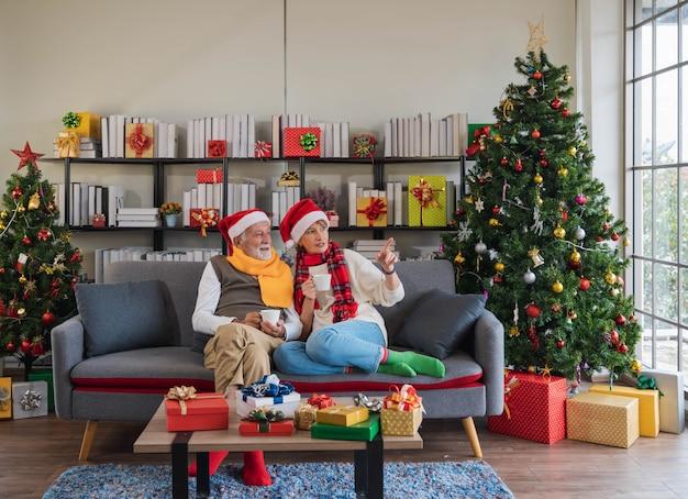 산타 모자를 쓴 백인 노인 부부는 집에서 뜨거운 음료를 들고 소파 소파에 앉아 아늑한 거실에 장식된 크리스마스 트리를 들고 창밖을 바라보고 있습니다. 휴식 휴가.