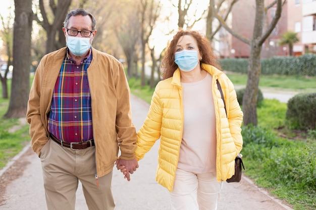 手をつないで公園を歩く年配の白人カップル。 2人とも保護マスクを着用。 covid-19パンデミックによる監禁からの解放の概念。