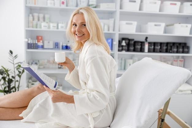 白いバスローブに笑みを浮かべて、美容院でお茶とパンフレットを持っているシニア白人女性。